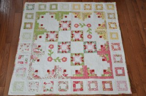 This is Nico's quilt Pastel Garden. It's made from the cutest Jelly Roll. I added the scraps of red and the white background fabric. It's an original design using some traditional log cabin blocks.