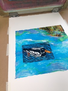 I've pulled the monoprint, in this case fabric dye painted on the silk screen, over a print I did in ink of my duck linocut. You can see that I masked off the shape of the duck before pulling the print.